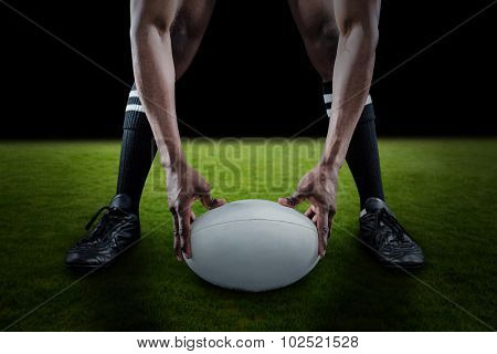 Low section of sportsman holding ball while playing rugby against green field