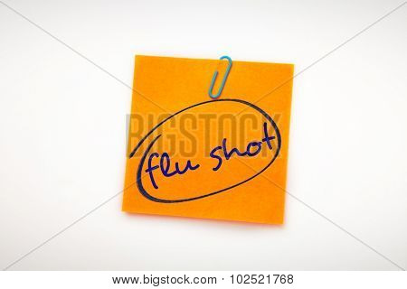 flu shots against orange adhesive note with a paperclip