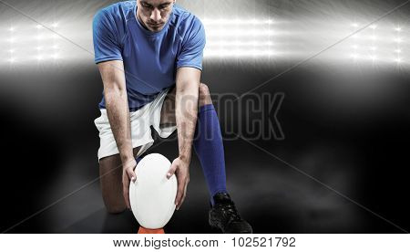 Full length of rugby player placing ball against spotlight
