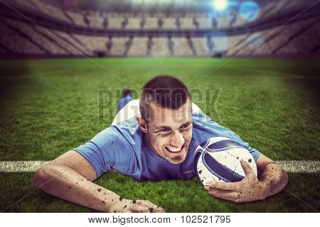 Confident rugby player lying in front with ball against large football stadium with lights