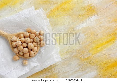 Still Life With Chickpea Seeds On Wooden Spoon And Paper Cloth