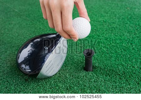 Close-up Hand Holding Golf Ball And A Golf Wood On A Driving Range