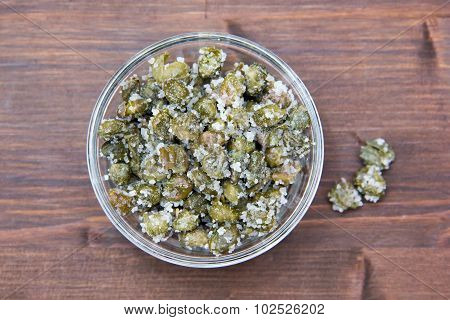 Salted capers in bowl on wood from above