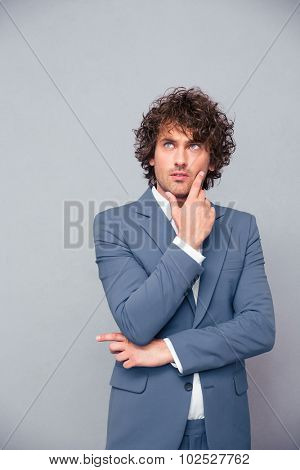 Portrait of a pensive businessman looking up over gray background