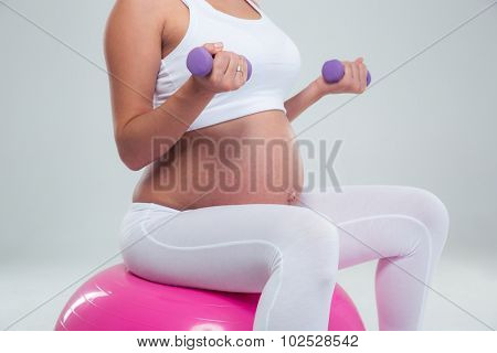 Portrait of a pregnant woman sitting on the fitness ball and workout with dumbbells isolated on a white background