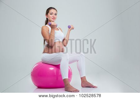 Portrait of a pregnant woman sitting on a fitness ball and workout with dumbbells isolated on a white background