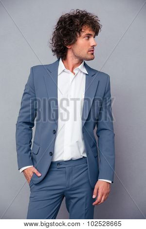Portrait of a pensive businessman looking away over gray background