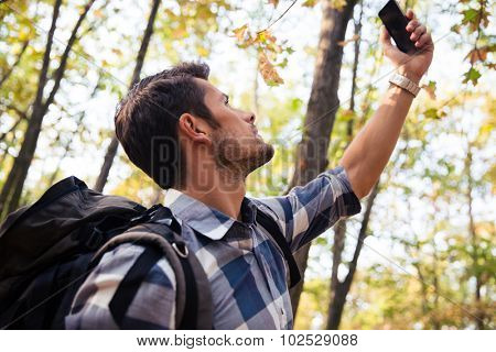 Portrait of a man searching connection on the phone in the forest