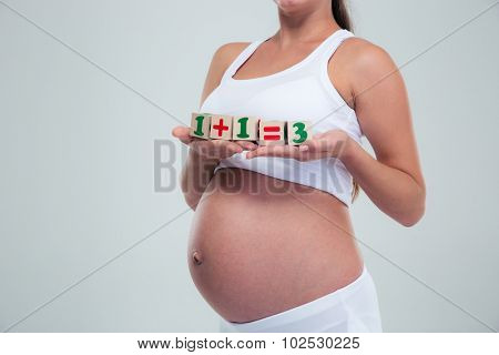 Closeup portrait of a pregnant woman holding bricks with equation 1 + 1 = 3 isolated on a white background