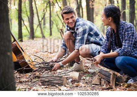 Portrait of a couple reading for bonfire in the forest