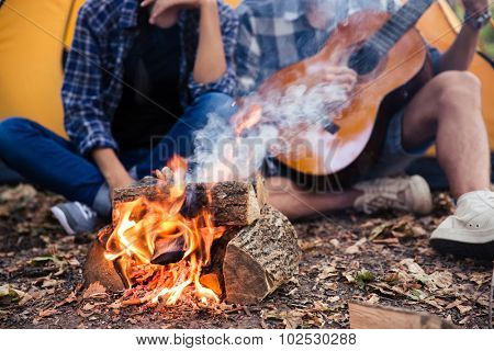 Closeup portrait of a couple sitting with guitar near bonfire in the forest