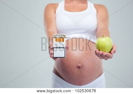 Concept image of a pregnant woman choosing beetwin cigarettes and apple isolated on a white background