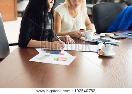 Two Young Business Woman Sign A Contract In The Office