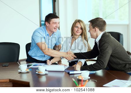 Smiling Man At A Business Meeting Shaking Hands With Each Other In The Office In The Presence Of A B