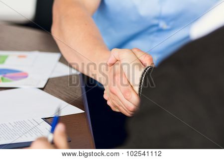 Handshake Of Two Businessmen On The Background Of  Secretary Of The Woman After Signing The Contract