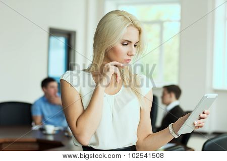Portrait Of Pensive Young Business Woman With A Tablet Computer At The Office At A Business Meeting