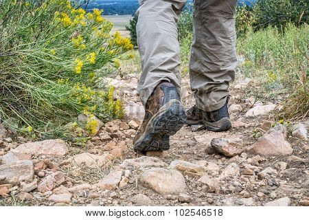 male feet in hiking leather boots on  a rocky mountain uphill trail