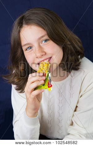 Beautiful teenage girl eating energy bar