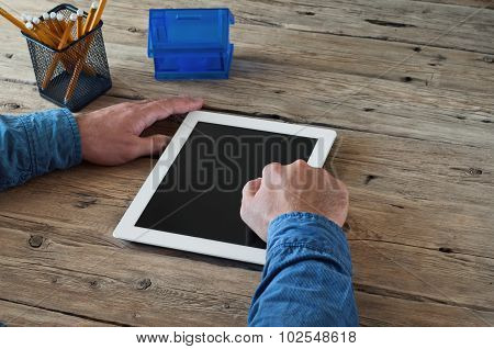Male Working At Home Using A Tablet Computer