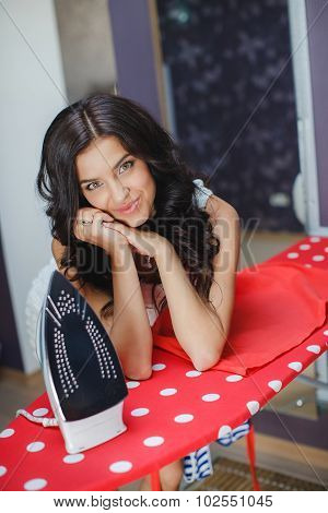 Happy young beautiful woman ironing clothes.