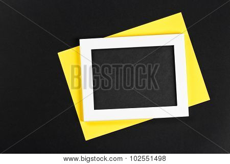 Horizontal White Photo Frame With Black Field And Yellow Paper Under Angle On Black Background Isola