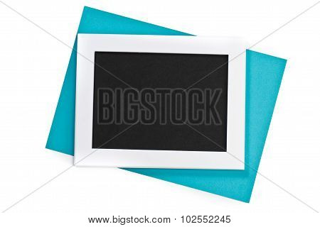 Horizontal White Photo Frame With Black Field And Blue Paper Under Angle On White Background Isolate
