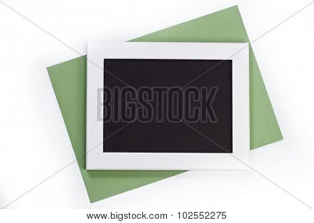 Horizontal White Photo Frame With Black Field And Green Paper Under Angle On White Background Isolat