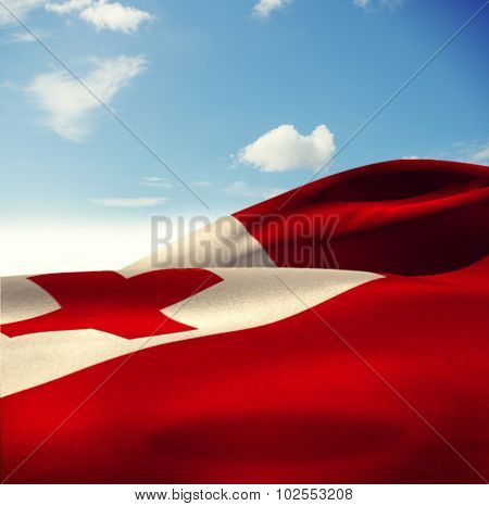 Waving Tonga flag against blue sky with clouds