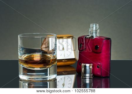 Glass of scotch and flask