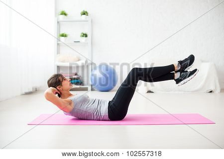 Woman doing abdominal crunches pilates exercise on mat at home.