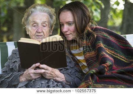 Grandmother and granddaughter reading a book while sitting in the Park.