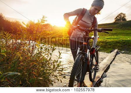Lady with bicycle crossing the river at sunset