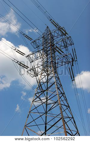 Electric Transmission Line Tower With Wires And Transformer Against The Bright Sky