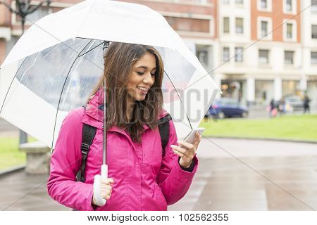 Smiling Woman With Umbrella Looking Her Cellphone In The Street.