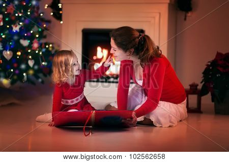 Mother And Daughter Reading On Christmas Eve At Fire Place