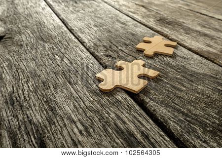 Two Puzzle Pieces Lying On Wooden Rustic Boards