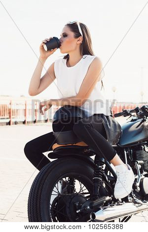 Girl With Cup Of Coffee Sitting On Vintage Custom Motorcycle
