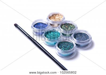Set of sparkling glitters in jars, selective focus, isolated on white background