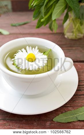 Cup of herbal tea with wild camomiles, mint and flowers