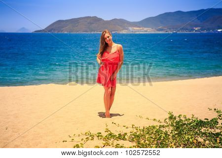 Blond Girl In Red Stands Barefoot On Sand Beach At Noon