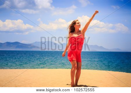 Blond Girl In Red Stands On Sand Beach Lifts Hand Up