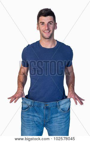 Handsome man showing loose denim jeans over white background
