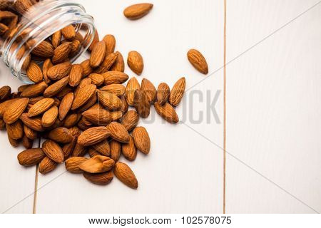 Overhead view of almonds spilling out of a jar on the table