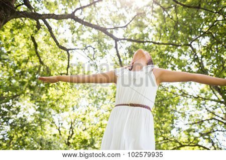 Low angle view of woman in white dress with arms outstretched against trees