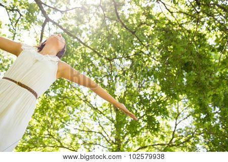 Low angle view of pretty woman with arms outstretched against trees in park