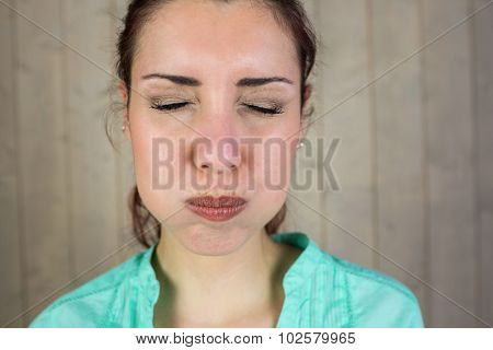 Close-up of woman with eyes closed while making face at home