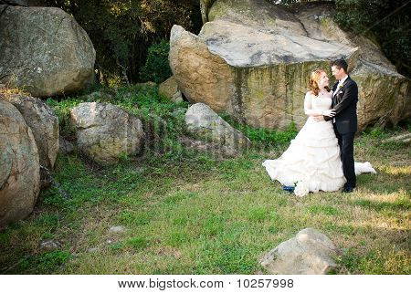bride and groom hugging standing outside next to rocks
