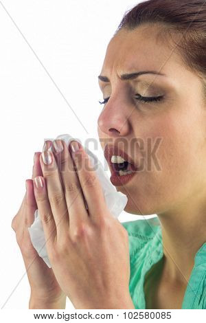 Sneezing woman holding tissue with mouth open against white background