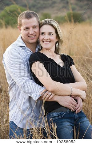 young sexy blond couple hugging and smiling in long grass