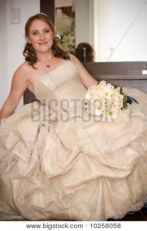 bride sitting leaning on arm smiling and holding white bouquet